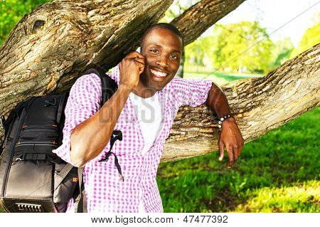 Young smiling african american man with rucksack in a park talking over mobile phone