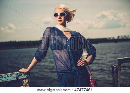 Stylish beautiful blond woman wearing white scarf and sunglasses  standing near rails of old pier