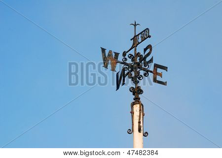 Rusty weather vane on top of pole in cloudless blue sky
