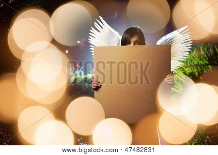 Angel woman with white wings holding blank cardboard message board poster over glowing golden lights background.