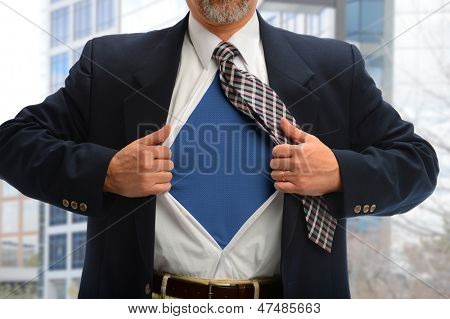 Businessman opening shirt to reveal super hero costume with buildings in background