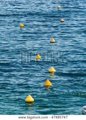 yellow buoys floating in the sea as a boundary