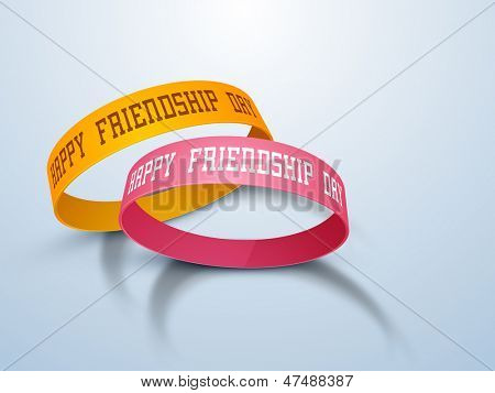 Happy friendship day concept with two friendship band on blue background.
