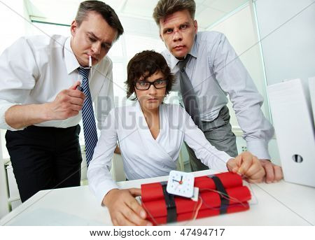 Group of businesspeople looking at camera with dynamite on workplace