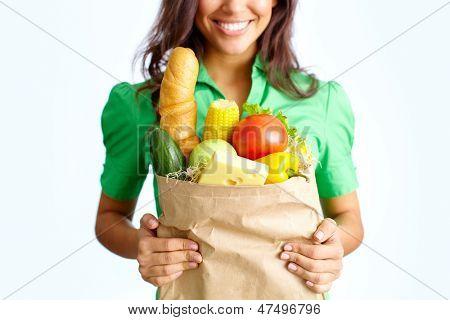 Imagem de papel grande saco cheio de diferentes frutas e legumes em mãos femininas