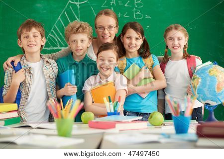 Portrait of cute schoolchildren and their teacher on background of blackboard