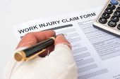 stock photo of reimbursement  - filling up a work injury claim form - JPG