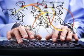 image of superimpose  - Closeup view of a mans hands typing on a computer keyboard with a superimposed world map showing a social media and networking concept - JPG