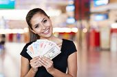 foto of gambler  - attractive young woman holding cash outside casino - JPG