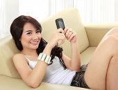 foto of handphone  - smiling young girl sitting on sofa and hold the handphone - JPG