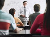 stock photo of middle class  - Teacher with a group of high school students in classroom - JPG