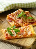 pizza of puff pastry with tomato sauce and parsley