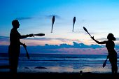 stock photo of juggling  - Man and woman juggling on the ocean beach at sunset - JPG
