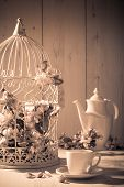 stock photo of edwardian  - Afternoon tea with birdcage filled with apple blossom in background  - JPG