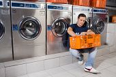 Young man with basket of clothes sitting against washing machines at laundromat