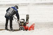 stock photo of snow shovel  - Worker removes snow with hand snowblower - JPG