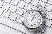 stock photo of stopwatch  - Close up of analog stopwatch on a laptop keyboard with copy space - JPG
