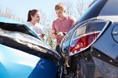 stock photo of annoyance  - Two Drivers Inspecting Damage After Traffic Accident - JPG