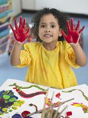 picture of finger-painting  - Portrait of cute little girl finger painting in art class - JPG