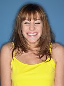 Closeup of a young woman in yellow tank top smiling against white background