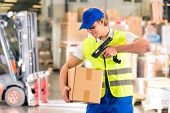 Warehouseman with protective vest and scanner, scans bar-code of package, he standing at warehouse o