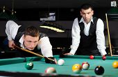 foto of snooker  - young professional people play snooker in the billiard club dark - JPG