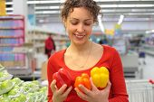 Young Woman In Shop With Sweet Peppers