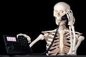 stock photo of gag  - A skeletal call centre employee keeps a call on hold forever - JPG