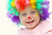 stock photo of circus clown  - A cute smiling baby boy is dressed up in a clown wig with clown make up face paint - JPG