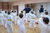 stock photo of karate  - karate boys training in sport hall focus on left boy in yellow belt - JPG