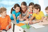pic of diligent  - Portrait of diligent schoolkids and their teacher interacting at lesson - JPG