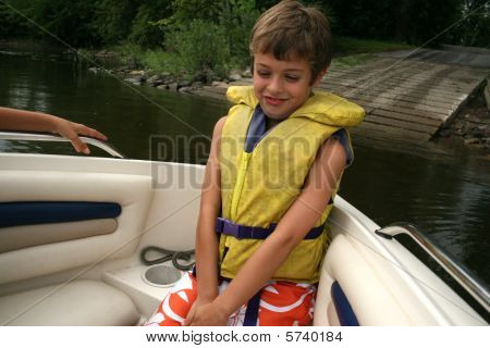Boy in a yellow lifevest smiling on a boat