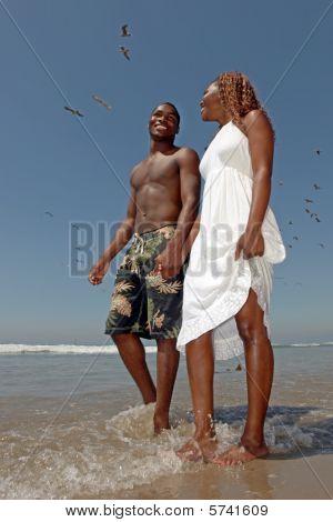 Beautiful Happy Couple Walking Along The Beach