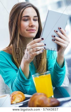 Pretty Woman Using Tablet While Having Breakfast In Coffee Shop