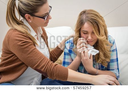 Mother soothes sad teen daughter crying