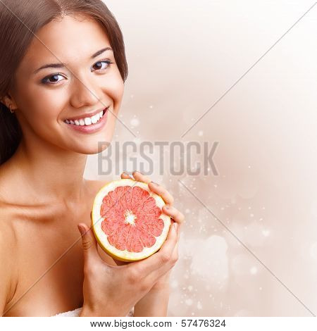 beautiful woman holding half of grapefruit