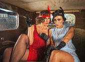 image of gangster necklace  - Two serious retro flapper women smoking in antique car - JPG
