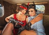 stock photo of tommy-gun  - Pair of pretty 1920s female gangsters in car - JPG