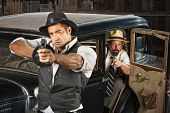 stock photo of tommy-gun  - Tough 1920s vintage gangsters outside aiming guns from car - JPG