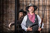 stock photo of bandit  - Sheriff Stands Stern in Front of a Jail Cell - JPG