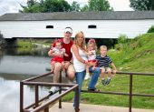 stock photo of covered bridge  - Family of five pose in front of the Elizabethton Covered Bridge in Tennessee - JPG