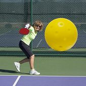 image of pickleball  - Digital image of senior female pickleball player hitting backhand shot directly at the camera - JPG