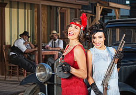 stock photo of tommy-gun  - Pair of laughing 1920s gangster women with guns  - JPG