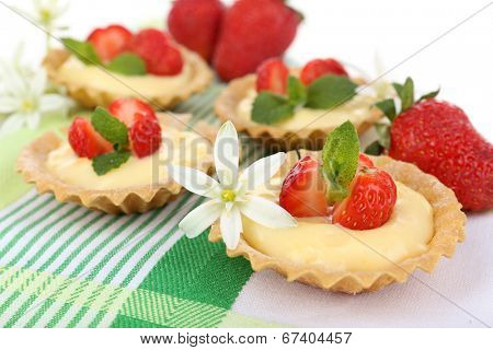 Tasty tartlets with strawberries on table close-up