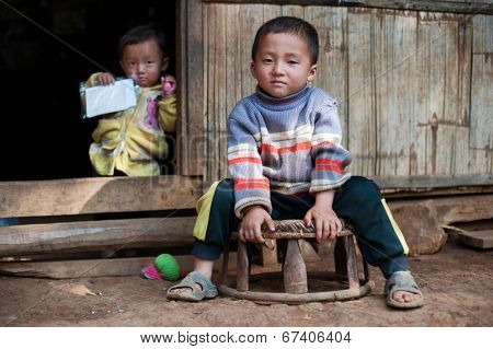 LUANG PRABANG, LAOS - 9 DEC, 2014: Unidentified two kids in traditional village of Laos. Eco tourism is popular tourist attraction in Asia