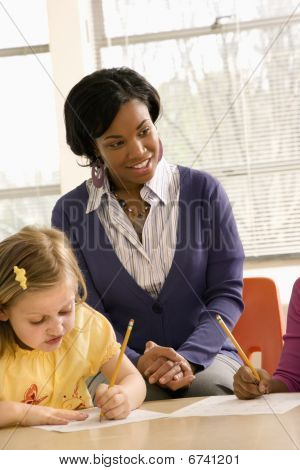 Teacher Smiling And Helping Students With Schoolwork