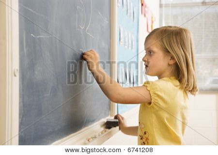Girl Doing Math On Blackboard