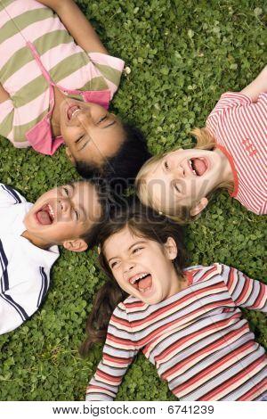 Kinder in Clover zusammen mit Köpfe schreien liegen