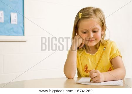 Young Girl Smiling In Classroom Writing On Paper