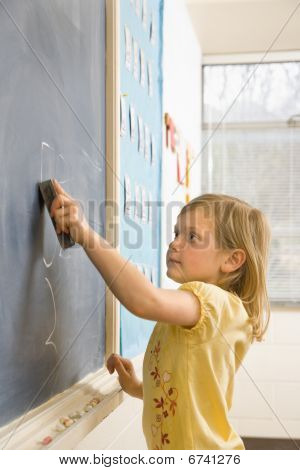 Girl Erasing Writing On Blackboard